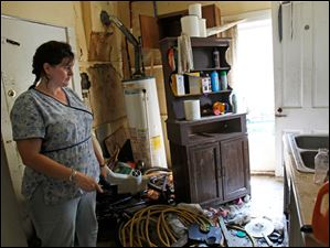 Nancy Grove shows the kitchen where burglars broke into through the window at the home she owns in Toledo.