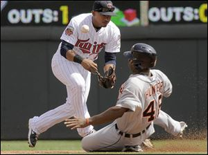 Minnesota Twins shortstop Eduardo Escobar, left, mishandles the throw as Detroit Tigers' Torii Hunter, right, slides in safely on a fielder's choice.