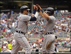 Detroit Tigers' Ian Kinsler, right, congratulates Victor Martinez, left, after scoring on Martinez two-run home run.