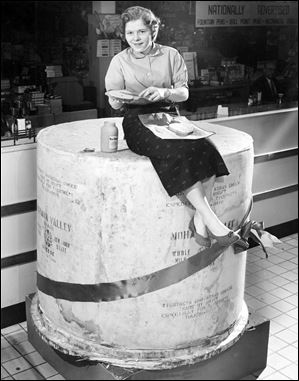 Preparing a cheese sandwich atop Tiedtke's annual Christmas 2-ton cheese is Evelyn Durdel in this 1955 file photo. The cheese was 5 feet high and 4 and a half feet in diameter.