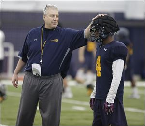 Jon Heacock, University of Toledo football team's assistant head coach/defensive coordinator/safeties coach talks to Corey Jones, during spring practice.