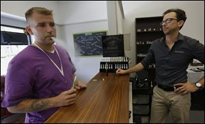 Toledoan Joe Destazio, left, tests various vapor flavors at the NiceCloud ecigarette store in Toledo. Watching is store owner Brad Everett, who mixes the flavors himself.