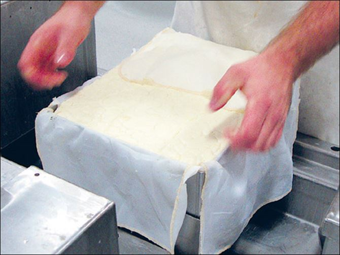 Cheese is pressed into a m Cheese is pressed into a mold to remove liquid at Henning's cheese factory.
