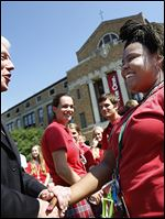 Bishop Thomas, 55, greets Central Catholic High School senior A'yanna Bishop outside the school on Cherry Street. She was shooting yearbook pictures.