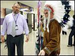 Waite High School principal Todd Deem greets senior Jason Kendall, who is dressed as the school's Indian mascot, while young Kendall helps out with the freshman orientation Tuesday.