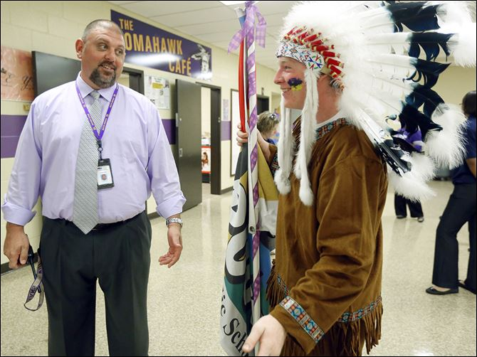 n4indiana Waite High School principal Todd Deem greets senior Jason Kendall, who is dressed as the school's Indian mascot, while young Kendall helps out with the freshman orientation Tuesday.