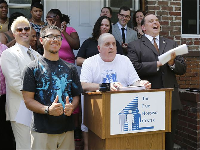 n4roofs-6 Paul Vagts speaks at the podium outside his Cherry Street home as his stepson, Kyle Hammond, gives a thumbs up. Behind them are Michael Marsh from the Toledo Fair Housing Center, left, and Wade Kapszukiewicz, chairman of the Lucas County Land Bank.