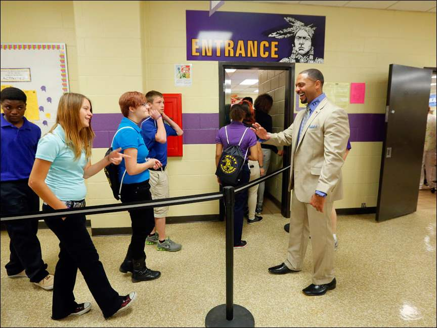 Dr. Romules Durant greets students in the cafeteria on the first day of school for freshman at Waite High School.