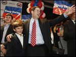 State treasurer and former CEO Doug Ducey, right, hugs his son Sam Ducey, with other son Joe Ducey, left, joining them as they all smile as the candidate arrives to claim victory on winning the Republican primary for Arizona governor Tuesday, Aug. 26, 2014, in Phoenix.  Ducey defeated five other Republican candidates and will face Democrat Fred DuVal, who was unopposed in the primary, in November. (AP Photo/Ross D. Franklin)