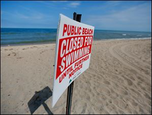 A sign announces that the public beach is closed for swimming.