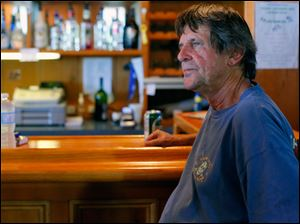 Richard Hamm, owner of Scudder Beach Bar and Grill, sits at his bar with a bottle of water.