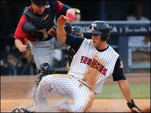 Toledo Mud Hens third baseman Wade Gaynor scores against Columbus Clippers catcher Luke Carlin during the fifth inning.