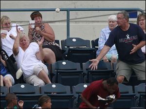 Fans duck when a foul ball goes their way on the upper deck of the 3rd base side of the stadium.
