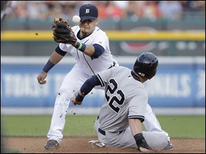 Detroit Tigers shortstop Eugenio Suarez, left, cannot handle the throw as New York Yankees' Jacoby Ellsbury (22) steals second base.
