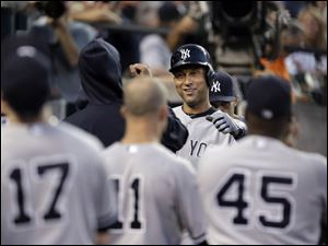 New York Yankees' Derek Jeter celebrates after scoring on a Mark Teixeira double against the Detroit Tigers.