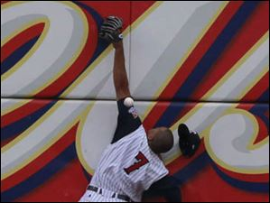 Toledo left fielder Danny Fields makes a high leap against the wall in an attempt to catch a ball during game against Columbus.