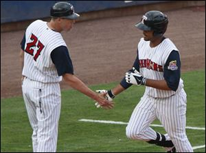 3rd base coach Mike Hessman shakes hands with Danny Fields after he hit a home run.