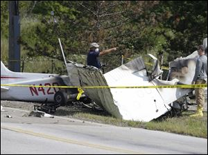 Investigators look over the wreckage of a plane crash as it rests on the side of a road.
