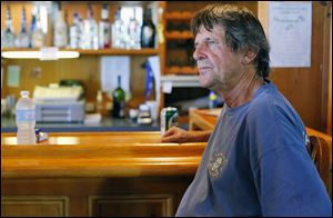Richard Hamm, at the bar of his Scudder Beach Bar and Grill on Pelee Island, keeps calm about water quality concerns, even as a big tourism weekend approaches.