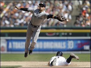 Detroit Tigers' Ian Kinsler steals second base as New York Yankees second baseman Martin Prado can't reach the throw from catcher Brian McCann.
