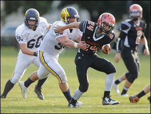 Summerfield player Chase Pirolli (24) tries to break free from Erie Mason player Bobby Livernois (50).