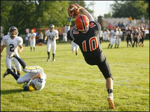 Summerfield player Josh Van Kainen (10) hauls in a pass in the end zone against Erie Mason's Baile Dominique (20).