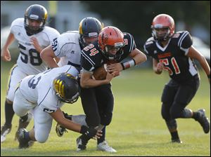 Summerfield's Chase Pirolli (24) is tackled by Erie Mason players Sean Strickler (63) and Bobby Livernois (50).