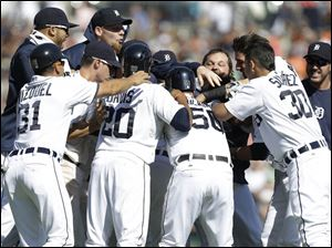 Detroit Tigers' Alex Avila celebrates with teammates after hitting a walk off single to score Bryan Holladay.