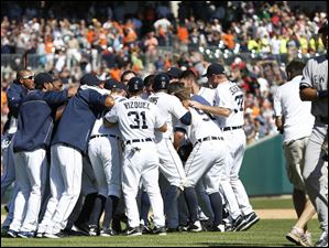 New York Yankees shortstop Derek Jeter, right, walks off the field as Detroit Tigers' Alex Avila celebrates with teammates after hitting a walk off single to score Bryan Holladay.
