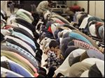 Worshippers bow for Asr, or afternoon prayer,  at the 51st annual Islamic Society of North America Convention at Cobo Center in Detroit. Former President Jimmy Carter is to present the keynote speech today. The convention concludes Monday.