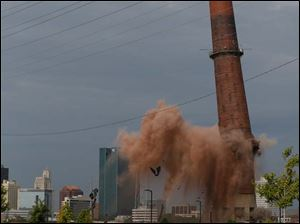 A portion of the last smokestack at the site of the former Toledo Edison Power Plant in East Toledo is imploded Friday.