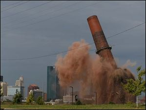 A portion of the last smokestack at the Toledo Edison Power Plant in East Toledo is imploded Friday.