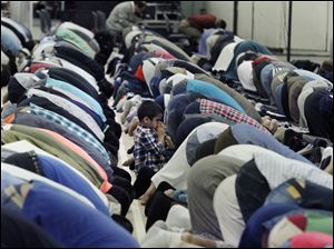 A child kneels beside worshippers who are bowing during Asr, or afternoon prayer.