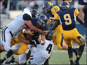 Whitmer QB Chase Bodeman (6) is brought down by Perrysburg LB Chaz Westfall and Evan Conley (4).