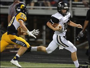 Perrysburg QB Gus Dimmerling (10) runs for a 51-yard touchdown and pst Whitmer DB Mitchell Kubicki (20).