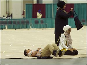 A child relaxes on the prayer mat, as women complete their Asr, or afternoon prayer.
