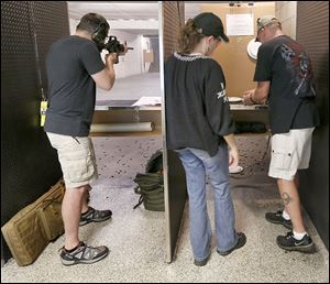 Army infantryman Geoff Earnhart of Perrysburg aims his AR15 Smith & Wesson M&P 15 at Shooters of Maumee. At right are Kelly and Brian Smith of Toledo.