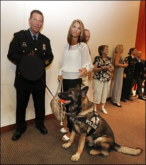 Toledo police Sgt. Joseph Taylor, his wife Amie, and Sgt. Joker attend a ceremony in which both sergeants were promoted.