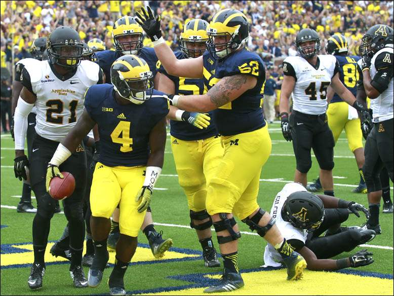 Michigan's De'Veon Smith is congratulated by Mason Cole after Smith scored a touchdown.