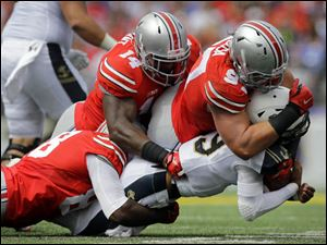Ohio State defensive lineman Steve Miller, from left, linebacker Curtis Grant and defensive lineman Joey Bosa sack Navy quarterback Keenan Reynolds.