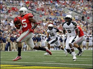 Ohio State running back Ezekiel Elliott, left, runs past Navy safety Parrish Gaines (2) and linebacker Chris Johnson (46) for a touchdown.