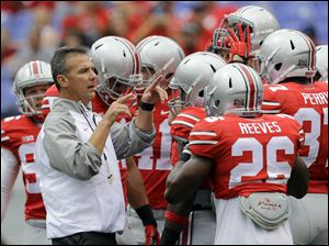 Ohio State head coach Urban Meyer, left, gathers with his players before the game.