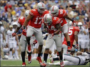 Ohio State linebacker Curtis Grant (14) celebrates with teammates after tackling Navy quarterback Keenan Reynolds.