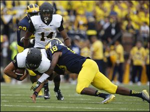 Appalachian State quarterback Taylor Lamb is tackled by Michigan's A.J. Pearson.