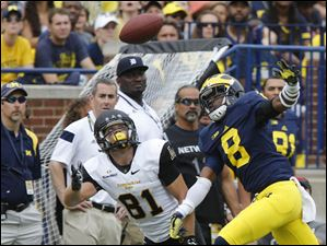 A pass to Appalachian State's Bobo Beathard is broken up by Michigan's Channing Stribling.