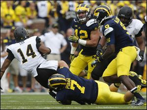 Appalachian State's Marcus Cox is tackled by Michigan's Henry Poggi.