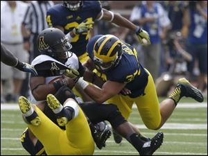 Appalachian State's quarterback Kameron Bryant is sacked by Michigan's Desmond Morgan, bottom, and Joe Bolden.