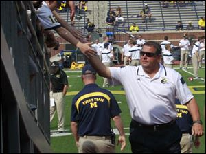 Michigan head coach Brady Hoke shakes hands with fans as he enters the tunnel at the Michigan Stadium.