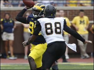 Michigan quarterback Devin Gardner throws under pressure from Appalachian State's John Law.