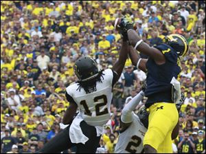 Michigan's Devin Funchess leaps over Appalachan's Jordan Ford, 12, and Doug Middleton to catch a touchdown pass.
